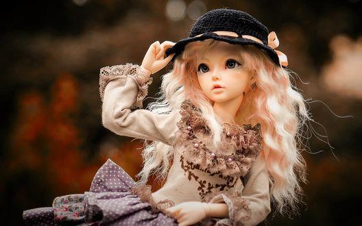 Обои Красивая кукла в шляпке на размытом фоне