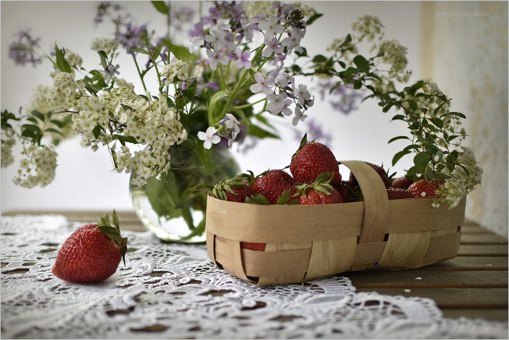 Обои для рабочего стола На столе с белой скатертью лежит в плетеной корзине клубника, рядом ваза с цветами, фотограф Шипунова Ирина