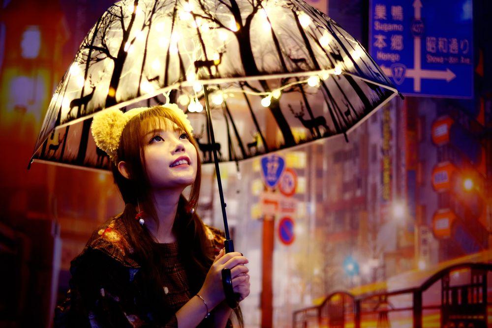 Обои для рабочего стола Девушка в плюшевом ободке смотрит на рисунок зонта, освещаемый гирляндой