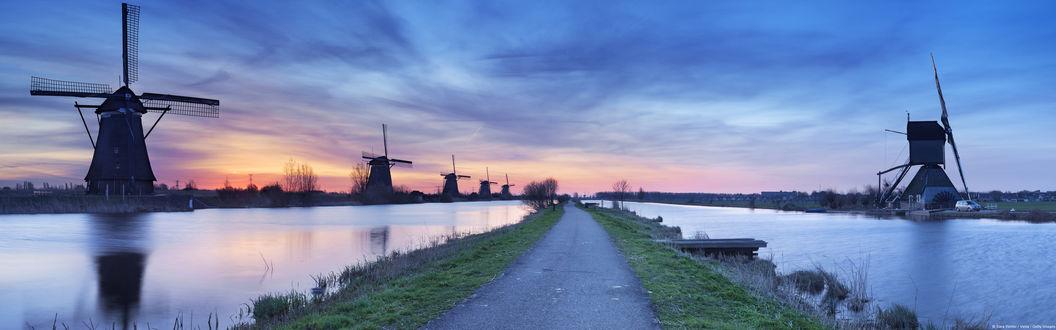 Обои Ветряные мельницы, стоящие на берегу реки на фоне вечернего небосклона