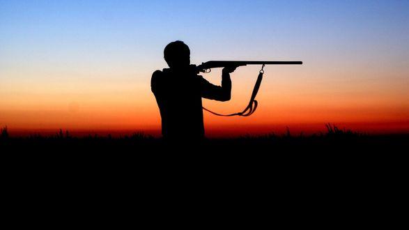 Обои Силуэт мужчины с ружьем в вечернем поле
