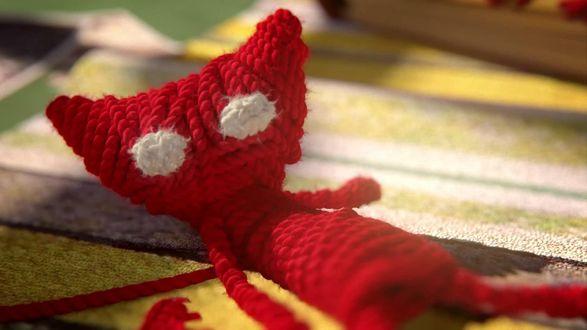 Обои Игрушечный кот из красной веревки лежит спиной на коврике, unravel-мультиплатформенная компьютерная игра в жанре пазл-платформер, разработанная шведской студией Coldwood Interactive