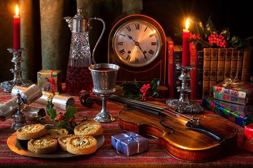 Обои Красивый натюрморт - тарелка с пирожными, бокал с вином, скрипка, коробки с подарками, книги и настольные часы, все это освещается свечами в серебряных подсвечниках, автор Marcus Rodriguez