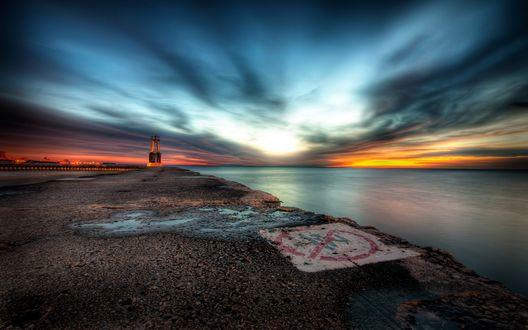 Обои Побережье моря на закате солнца, на горизонте маяк
