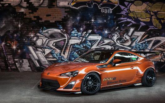 Обои Nissan GT-R стоит на фоне стены с граффити