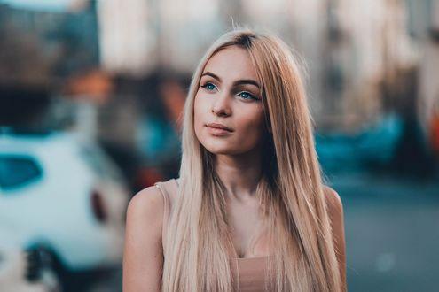 Обои Красивая девушка с распущенными волосами стоит на размытом фоне улицы