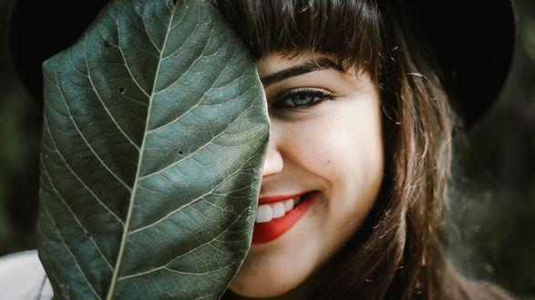 Обои Улыбающаяся девушка спрятала пол-лица за большим зеленым листом
