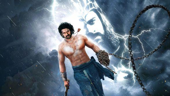Обои Главный герой фильма Бахубали Завершение – Шива (Прабхас) идет с мечом и цепью, за ним виден светящийся контур воина в доспехах