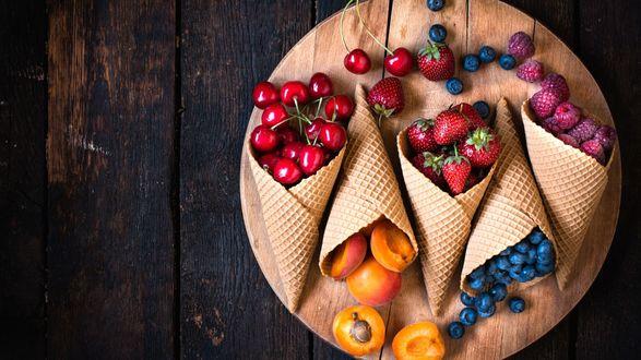 Обои Вафельные рожки с вишнями, абрикосами, малиной, клубникой, сливами лежат на деревянной тарелке