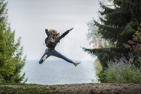 Обои Девушка с рюкзаком за спиной в прыжке на фоне природы, фотограф Себастьян Воортман