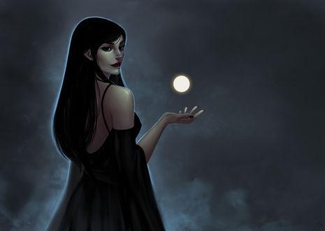 Обои Темноволосая девушка в черном платье держит руку над шаром,
