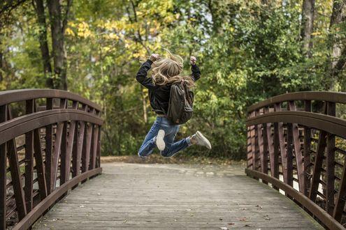 Обои Девушка с рюкзаком за спиной в прыжке на фоне природы, на мосту, фотограф Себастьян Воортман