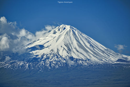 Обои Заснеженная вершина горы на фоне голубого неба с облаками. Фотограф Tiko Aramyan
