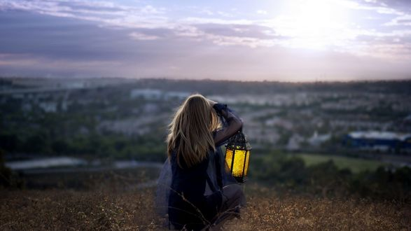 Обои Девушка с фонарем в руке сидит на фоне города вдалеке