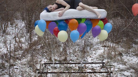 Обои На разноцветных шарах на матрасе лежит девушка