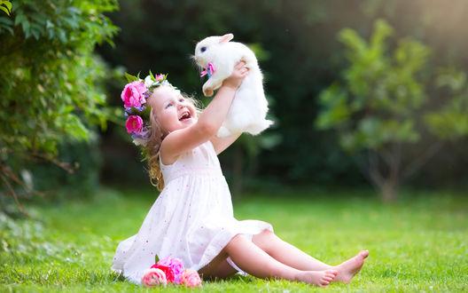 Обои Маленькая девочка в белом платье и венке из цветов подняла вверх белого кролика и смеется, сидя на траве