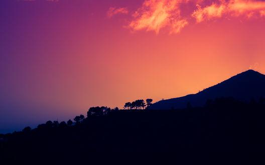 Обои Темно-фиолетовые силуэты гор на фоне ярко-оранжевого заката