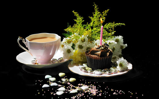 Обои Чашка кофе стоит рядом с букетом и праздничным кексом со свечой на черном столике