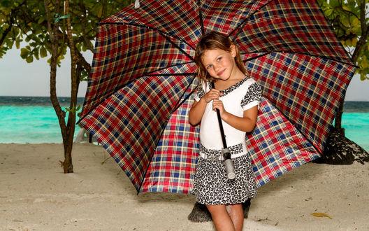 Обои Улыбающаяся девочка стоит под большим клетчатым зонтом на берегу залива