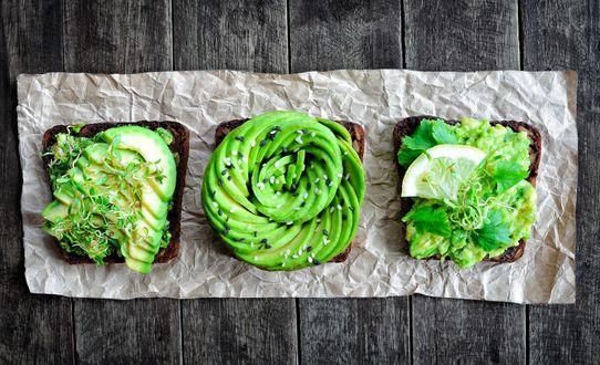 Обои Три бутерброда из черного хлеба с авокадо, ростками пшеницы и долькой лимона на деревянной поверхности