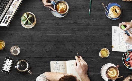 Обои Рабочий круглый стол, на котором видны руки с блокнотами и ручками, клавиатуры, чашки с кофе и чаем, блюдечки с булочками