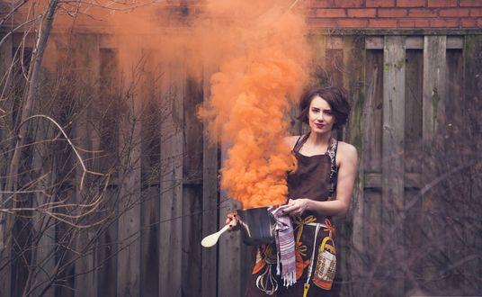 Обои Девушка стоит перед забором дома, в руках у нее пылающая кастрюлька из которой валит оранжевый дым, автор Matt Wiebe