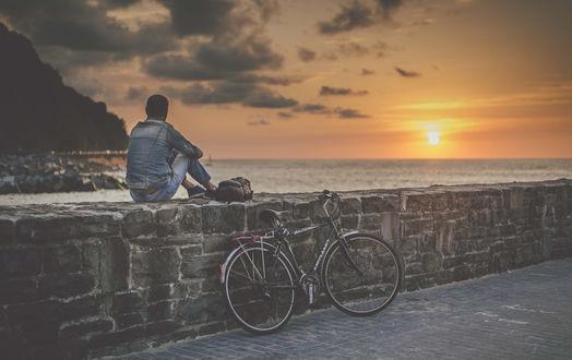 Обои Парень сидит на перилах моста набережной и наблюдает за закатом