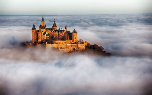 Обои Замок на горе в окружении облаков