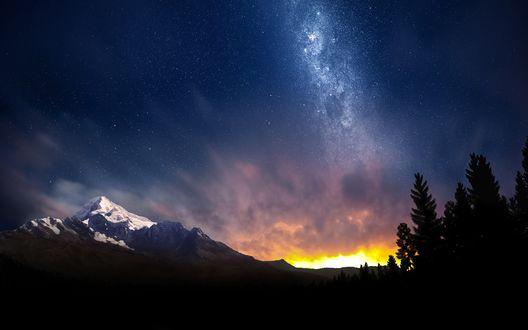 Обои Силуэты хвойных деревьев и заснеженные горы вдали, на фоне звездного неба с золотой вспышкой заходящего солнца