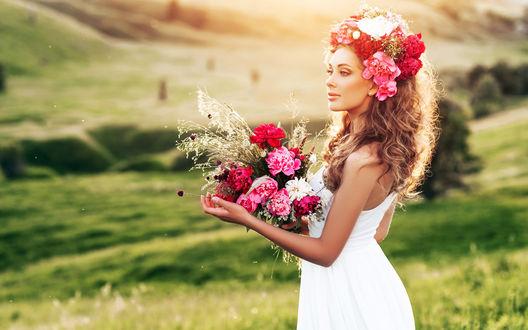 Обои Светловолосая девушка в венке из цветов и с букетом в руках в белом платье стоит на фоне размытого летнего пейзажа