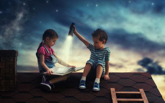 Обои Двое детей на крыше читают книгу ночью при свете фонаря