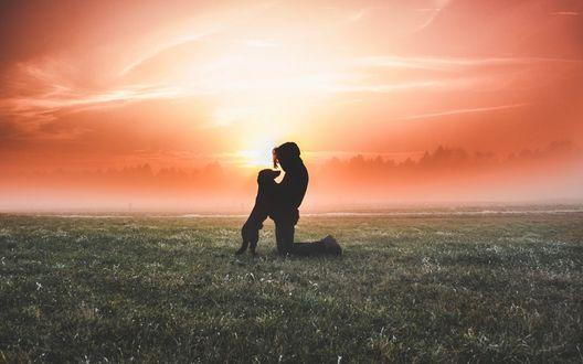 Обои Мужчина обнимает собаку на поле на фоне закатного неба