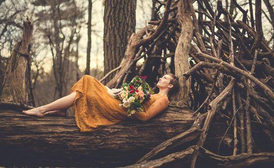 Обои Девушка в желтом платье с букетом цветов полулежит на стволе дерева рядом с шалашом и мечтательно смотрит вдаль