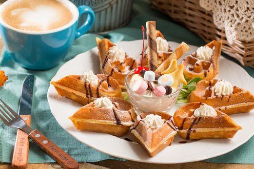 Обои Десерт из вафель с кремом и зефира разложен на тарелке рядом кофе, нож и вилка