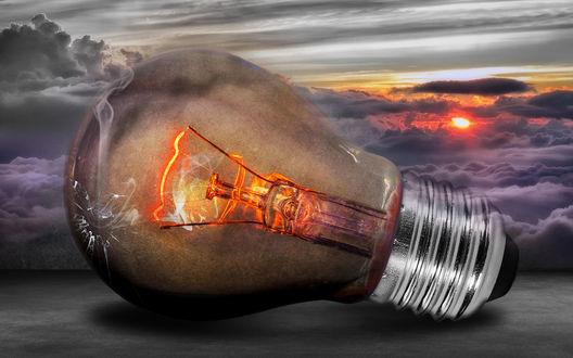 Обои Раскаленная докрасна лампочка на фоне заходящего солнца и клубящихся серых туч