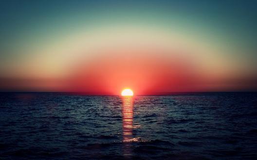 Обои Красное закатное солнце опускается в море, на котором простирается огненная дорожка