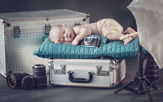 Обои Младенец рядом с фотоаппаратом спит на большом чемодане