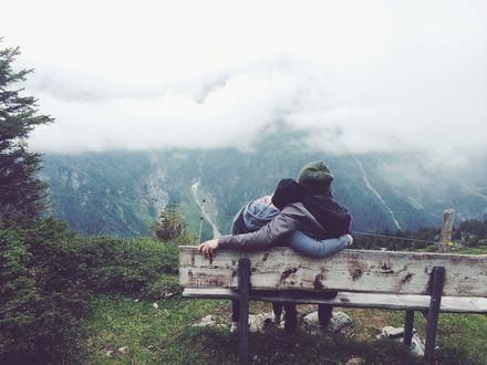 Обои Парочка сидит обнявшись на лавочке перед лицом горных вершин, которые скрывает клубящийся туман