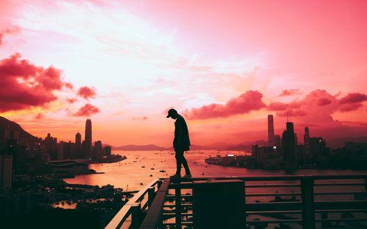 Обои Мужчина стоит на мостках над водоемом на фоне города и розового закатного неба, фотограф Anthony Intraversato