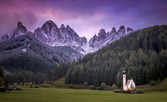 Обои Небольшая церковь St. Johann / Сан - Джованни белеет у подножия высоких гор с заснеженными вершинами на фоне лилового неба во время восхода солнца, South Tyrol / Южный Тироль, фотограф Dennis Fischer / Деннис Фишер