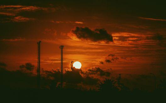 Обои Солнце заходит на фоне ярко-оранжевого закатного неба с небольшими тучками