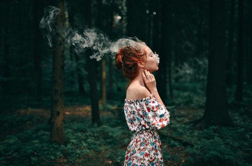 Обои Девушка, с выходящим со рта дымом, стоит на фоне леса. Фотограф Игорь Бурба