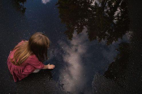 Обои Девочка присела около лужи, положив руку на воду, в которой отражаются деревья, by DANA LEIGH