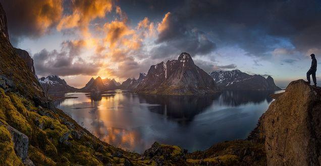 Обои Парень стоит на камне возле небольшого горного озера на Lofoten islands / Лофотенских островах, фотограф Janne Kahila