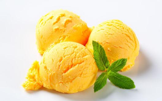 Обои Три шарика фруктового мороженого, украшенные листиками мяты на белом фоне