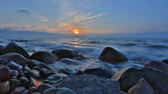 Обои Красивый морской пейзаж на фоне неба и догорающим солнцем на закате дня в легких облаках