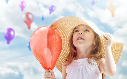 Обои Девочка в большой шляпе держит воздушный шарик и смотрит в небо, где летят такие же шарики