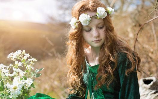 Обои Рыжеволосая девочка в зеленом платье и венке из белых цветов на фоне размытого пейзажа