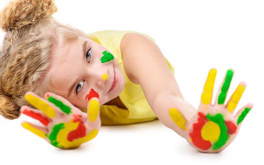 Обои Забавная кудрявая девочка протянула ладошки, разрисованные красками