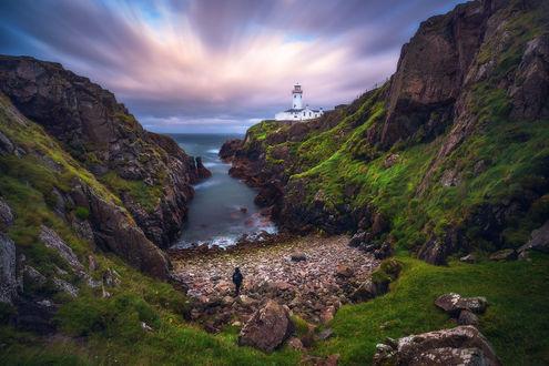 Обои Фотограф стоит между горными образованиями, на одном из которых расположен маяк, фотограф Daniel F